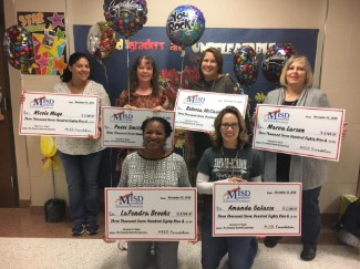 second grade teachers holding checks